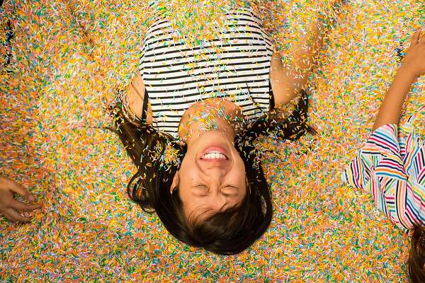 Michelle Wong is buried in sprinkles by her friends in the Sprinkle Pool at the Museum of Ice Cream in San Francisco, Calif., on Sunday, September 17, 2017. The pop-up exhibit opened to the public on Sunday.
