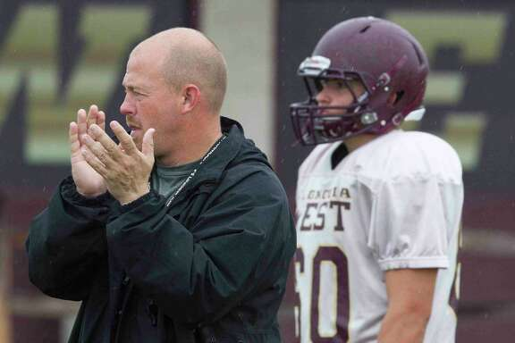 Magnolia West football coach J.D. Berna encourages his team during a practice.