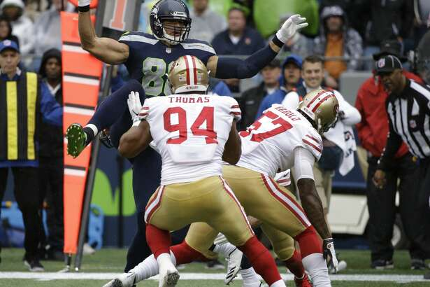 Seattle Seahawks tight end Jimmy Graham, upper left, leaps during a play against the San Francisco 49ers during the first half of an NFL football game, Sunday, Sept. 17, 2017, in Seattle. Graham went down with an injury after the play. (AP Photo/Elaine Thompson)