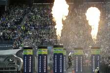 Seattle Seahawks defensive end Michael Bennett leaps as fire effects go off as he runs out of the tunnel before an NFL football game against the San Francisco 49ers, Sunday, Sept. 17, 2017, in Seattle. (AP Photo/John Froschauer)