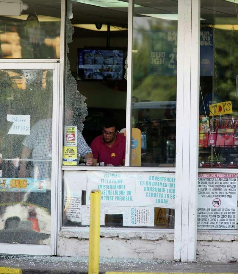 Personnel clean up shattered glass at the Hays Food Mart at the corner of North New Braunfels Avenue and Hays Street, Sunday, Sept. 17, 2017. Earlier in the morning, three people were shot in a drive-by shooting at the store. Photo: JERRY LARA, San Antonio Express-News / © 2017 San Antonio Express-News