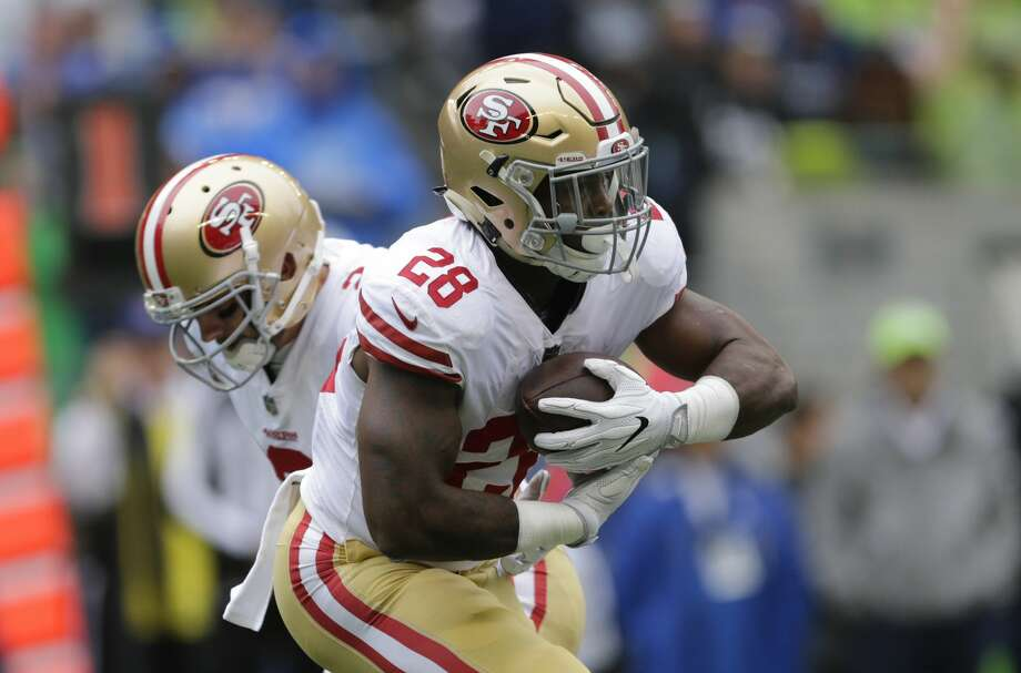 San Francisco 49ers running back Carlos Hyde (28) takes a handoff from quarterback Brian Hoyer, left, in the first half of an NFL football game, Sunday, Sept. 17, 2017, in Seattle. (AP Photo/John Froschauer) Photo: John Froschauer/AP