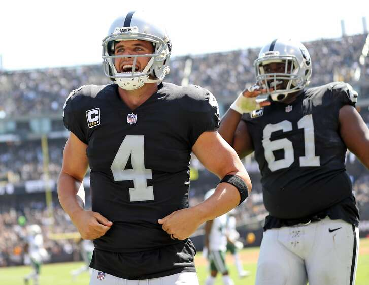 Oakland Raiders' Derek Carr smiles after Michael Crabtree's 2nd quarter touchdown catch with Jared Cook against New York Jets during NFL game at Oakland Coliseum in Oakland, Calif., on Sunday, September 17, 2017.