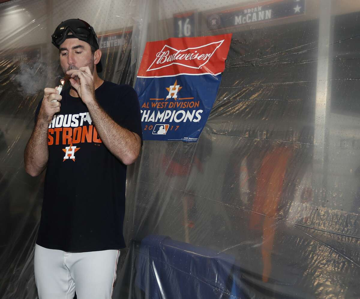 Houston Astros starting pitcher Justin Verlander (35) lights up a cigar in the clubhouse after they clinched the American League West crown after beating the Seattle Mariners 7-1 during an MLB baseball game at Minute Maid Park, Sunday, Sept. 17, 2017, in Houston. ( Karen Warren / Houston Chronicle )