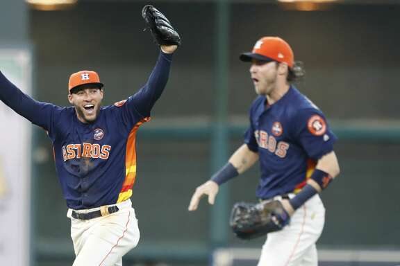 Houston Astros George Springer (4) runs with Josh Reddick (22) as he celebrated the final out after the Houston Astros clinched the American League West by beating the Seattle Mariners 7-1 during an MLB baseball game at Minute Maid Park, Sunday, Sept. 17, 2017, in Houston.  ( Karen Warren / Houston Chronicle )