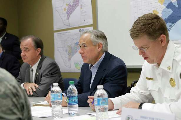 Texas Gov. Greg Abbott, center, and Commissioner John Sharp, seated second from left, receive a briefing on Hurricane Harvey recovery efforts at the new FEMA Joint Field Office, Thursday, Sept. 14, 2017, in Austin, Texas. (AP Photo/Eric Gay)