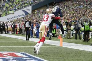 Seattle Seahawks wide receiver Paul Richardson comes down with a reception for a touchdown as he is tackled by San Francisco 49ers cornerback Rashard Robinson (33) in the second half of an NFL football game, Sunday, Sept. 17, 2017, in Seattle. (AP Photo/John Froschauer)
