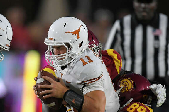 UT's Sam Ehlinger, top, is sacked by Southern California defensive lineman Christian Rector in the first half Saturday night.