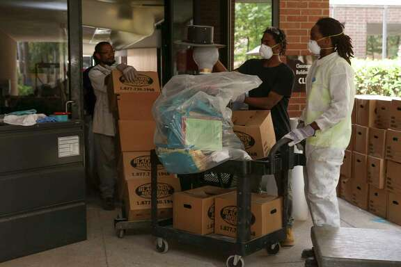 Workers remove salvaged classroom materials from Lone Star College-Kingwood's Classroom Building B during cleaning recently. Hurricane Harvey flooding has forced the college to move 73 percent of campus courses online.