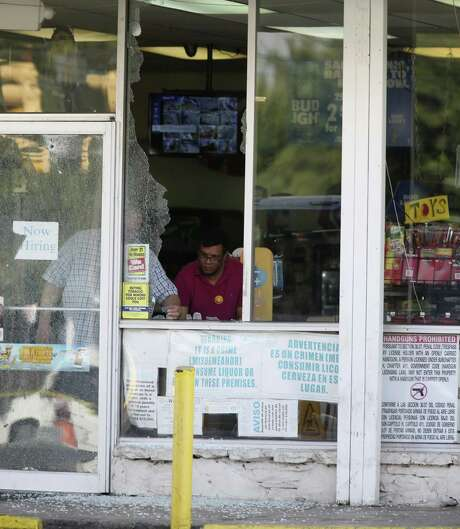 Personnel clean up shattered glass at the Hays Food Mart at the corner of North New Braunfels Avenue and Hays Street, Sunday, Sept. 17, 2017. Earlier in the morning, three people were shot in a drive-by shooting at the store. Photo: JERRY LARA, Staff / San Antonio Express-News / © 2017 San Antonio Express-News