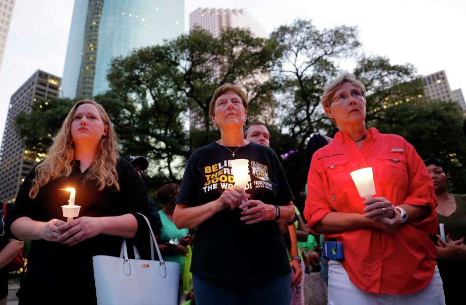 Kimberly Burris, Jane Meyer and Mary Brenda hold candles during a candlelight ceremony in honor of the victims of Hurricane Harvey, held on the steps of City Hall in Houston Sunday. Several dozen residents participated during the hour-long service. Photo: Michael Wyke, Freelance / © 2017 Houston Chronicle
