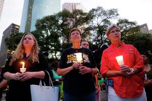 Kimberly Burris, Jane Meyer and Mary Brenda hold candles during a candlelight ceremony in honor of the victims of Hurricane Harvey, held on the steps of City Hall in Houston Sunday. Several dozen residents participated during the hour-long service.