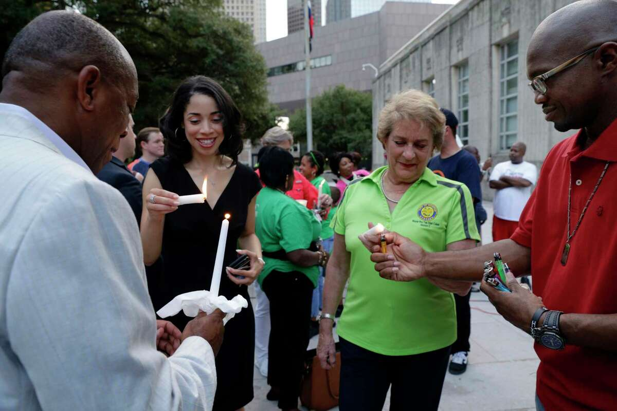 From left, Mayor Sylvester Turner, Amanda Edwards and Mayor Pro Tem Ellen Cohen get their candles lit by pastor V. Eric Gordon during a candlelight ceremony on the steps of City Hall Sunday night.