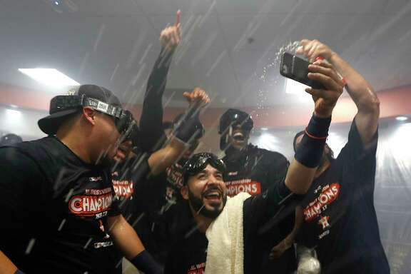 Marwin Gonzalez, center, takes a selfie with teammates amid streams of beer and Champagne on Sunday as the Astros celebrate clinching the AL West title.