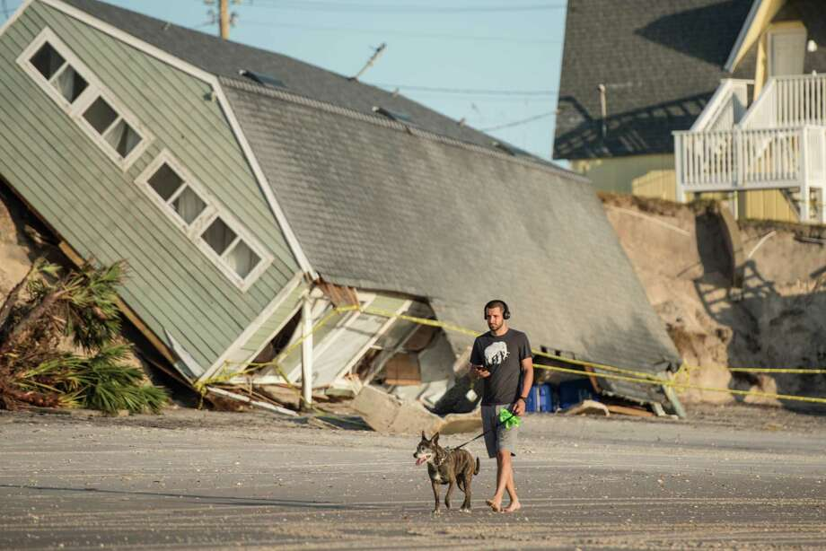VILANO BEACH, FL - SEPTEMBER 13: Jose Orosz walks his dog Karen by a beachfront home destroyed by Hurricane Irma on September 13, 2017 in Vilano Beach, Florida. Nearly 4 million people remained without power more than two days after Irma swept through the state.  (Photo by Sean Rayford/Getty Images) *** BESTPIX *** ORG XMIT: 775042414 Photo: Sean Rayford / 2017 Getty Images