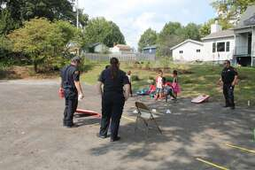 Members of the Edwardsville Fire Department toss bean bags with children on Saturday at Anchored in Truth Ministries' Love Fest. The church, located off Garfield Avenue in Edwardsville, hosted the event which featured games and inflatables for children, live music, food and more.