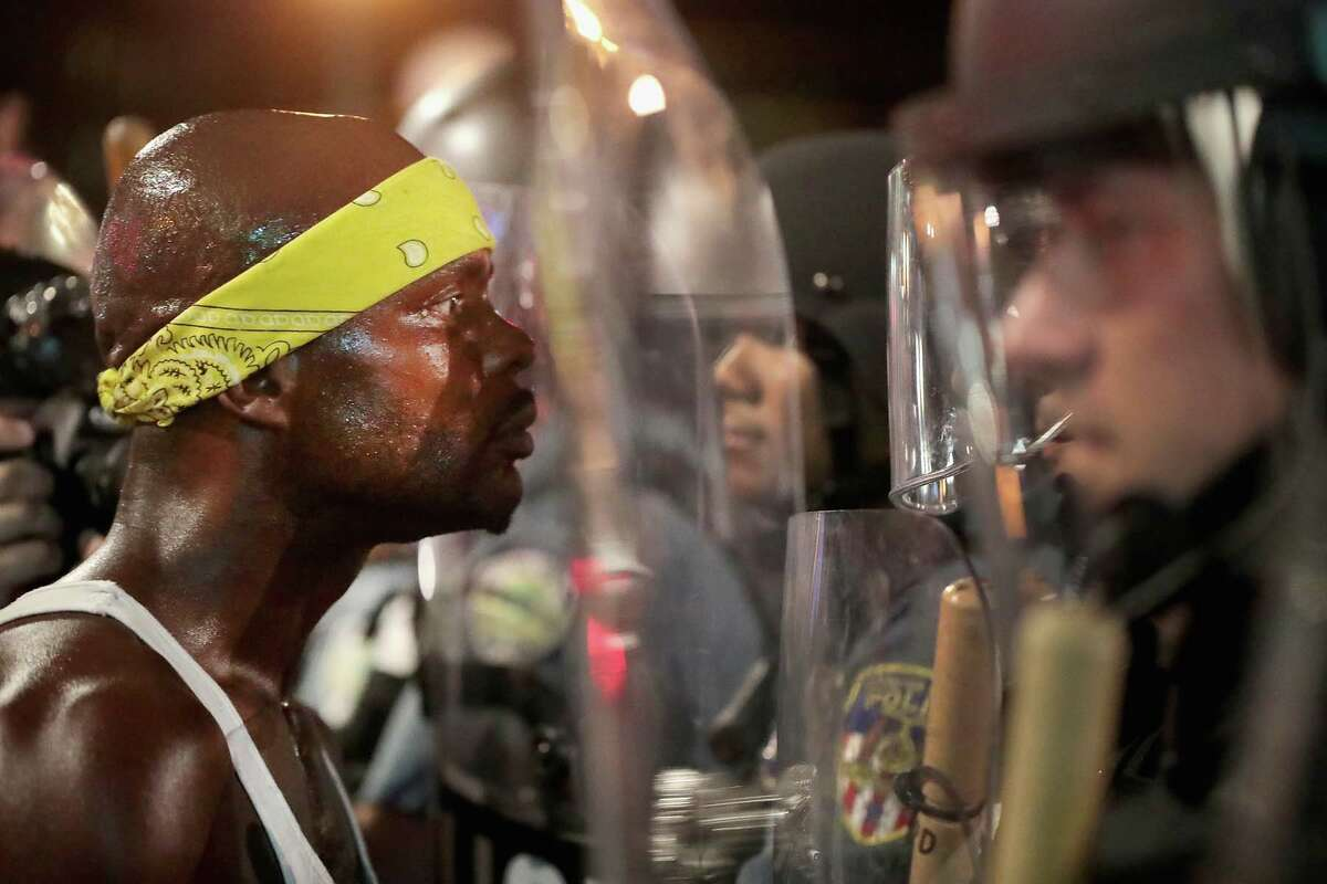 ST LOUIS, MO - SEPTEMBER 16: Demonstrators confront police while protesting the acquittal of former St. Louis police officer Jason Stockley on September 16, 2017 in St. Louis, Missouri. Dozens of business windows were smashed and at least two police cars were damaged during a second day of protests following the acquittal of Stockley, who was been charged with first-degree murder last year following the 2011 on-duty shooting of Anthony Lamar Smith. (Photo by Scott Olson/Getty Images)
