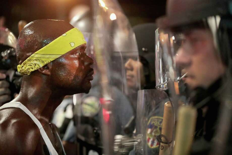 ST LOUIS, MO - SEPTEMBER 16:  Demonstrators confront police while protesting the acquittal of former St. Louis police officer Jason Stockley on September 16, 2017 in St. Louis, Missouri. Dozens of business windows were smashed and at least two police cars were damaged during a second day of protests following the acquittal of Stockley, who was been charged with first-degree murder last year following the 2011 on-duty shooting of Anthony Lamar Smith.  (Photo by Scott Olson/Getty Images) Photo: Scott Olson/Getty Images