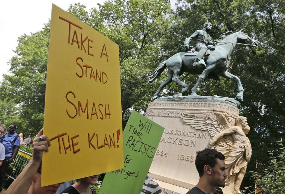 """FILE - In this July 8, 2017, file photo, protesters carry signs in front of a statue of Confederate Gen. Thomas """"Stonewall"""" Jackson as they demonstrate against a KKK rally in Justice Park in Charlottesville, Va. A resolution on removing the Jackson statue is on the Charlottesville City Council's agenda Tuesday night, Sept. 5, 2017. The city's decision earlier this year to remove a statue of Confederate Gen. Robert E. Lee helped spark a rally of white nationalists that descended into violence (AP Photo/Steve Helber, File) Photo: Steve Helber / Associated Press / Copyright 2017 The Associated Press. All rights reserved."""