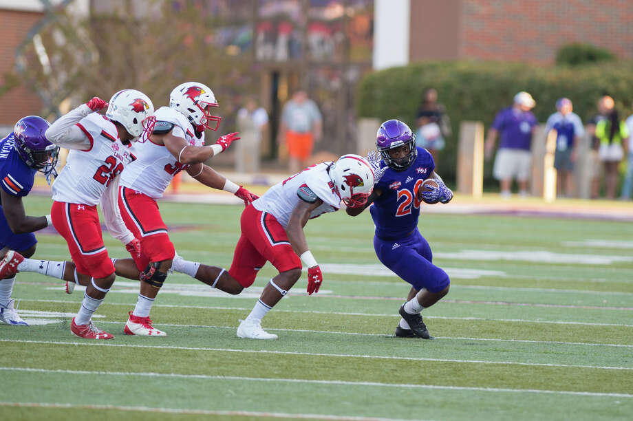 A group of Lamar defenders attempts to tackle Northwestern State running back Chris Jones during Saturday's conference opener at Turpin Stadium in Natchitoches. The Demons beat the Cardinals, 35-28. Photo: Northwestern State Athletics