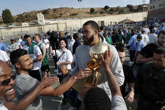 San Quentin Warriors players touch the Larry O'Brien Trophy held by JaVale McGee before members of the Golden State Warriors front office played a pick up game against the San Quentin Warriors in their annual trip to San Quentin Prison in San Quentin, Calif., on Friday, September 15, 2017.