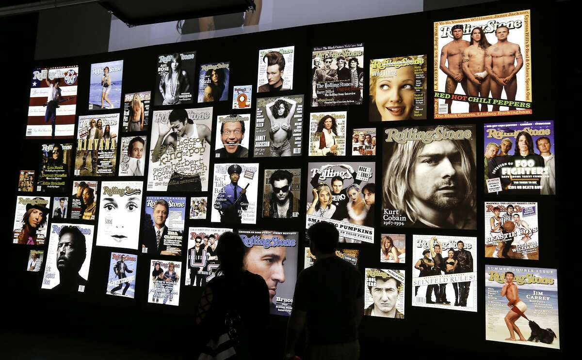 """This Tuesday, Aug. 29, 2017 photo shows people looking covers of the Rolling Stone magazines at the """"Rolling Stone 50 Years"""" exhibit at the Rock and Roll Hall of Fame, in Cleveland. (AP Photo/Tony Dejak)"""