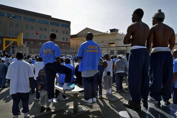 Inmates watch atop tables and seats as the Warriors play a pick up game against the San Quentin Warriors in their annual trip to San Quentin Prison in San Quentin, Calif., on Friday, September 15, 2017.