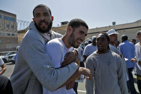 JaVale McGee hugs Georges Niand, center, after the Warriors played a pick up game against the San Quentin Warriors in their annual trip to San Quentin Prison in San Quentin, Calif., on Friday, September 15, 2017.