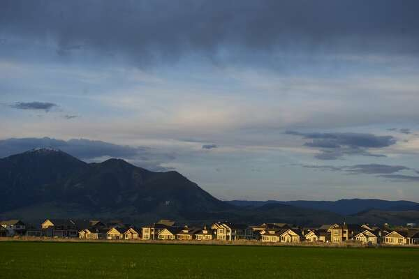 BOZEMAN, MT - MAY 22: The sun sets over a subdivision of homes with the 'M' on Baldy Mountain in the background on May 22, 2013 in Bozeman, Montana. The outskirts of Bozeman are being developed by new business and home construction. (Photo by Ann Hermes/The Christian Science Monitor via Getty Images)