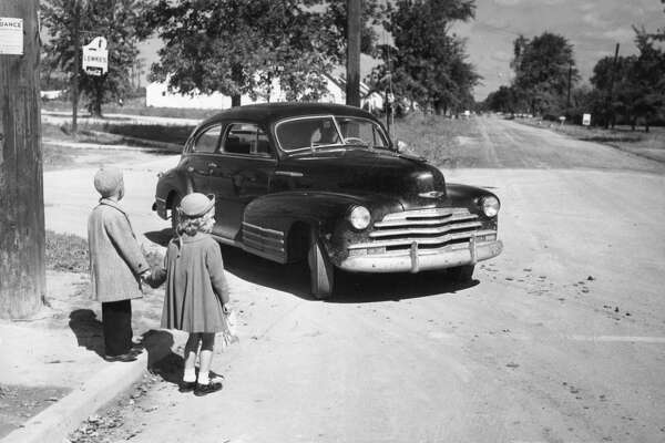 Motorists are urged to watch those sharp turns when rounding a corner. (From a 1949 special photo page on school safety.)