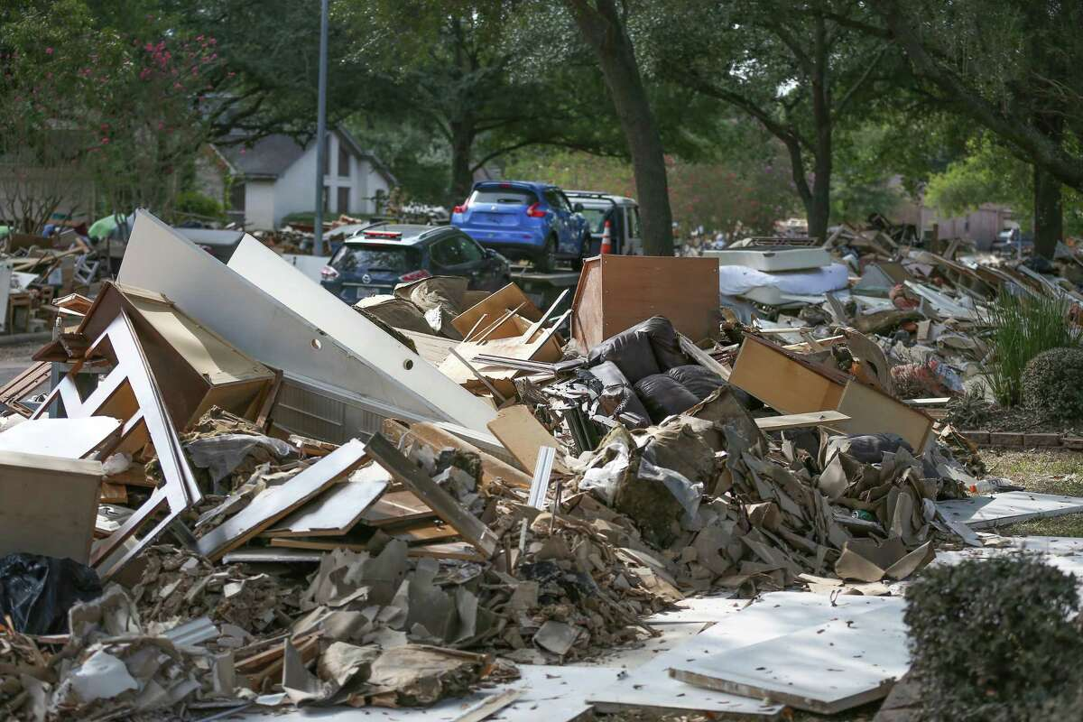 Debris lines the streets as FEMA team members go door to door connecting with people who need help, signing them up for disaster recovery assistance, answering questions Friday in Houston. ( Steve Gonzales / Houston Chronicle )