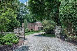 Stone pillars mark the entrance to the red brick colonial contemporary house at 53 Toilsome Hill Lane.