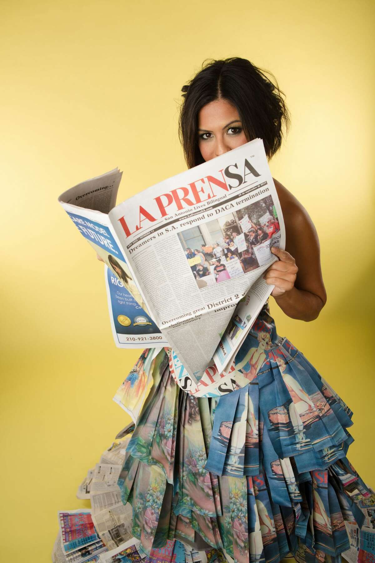 Nina Duran, daughter of late La Prensa publisher Tino Duran, wearing a dress made by Susie Hamilton from pages of the newspaper.