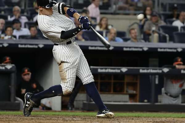 FILE - In this Sept. 14, 2017, file photo, New York Yankees' Aaron Judge hits a three-run home run during the fourth inning of a baseball game against the Baltimore Orioles, in New York. Nearly two decades after the height of the Steroids Era, Major League Baseball is on track to break its season record for home runs on Tuesday with nearly two weeks left in the season. There were 5,663 home runs hit through Sunday, 30 shy of the record 5,693 set in 2000.  (AP Photo/Frank Franklin II, File)