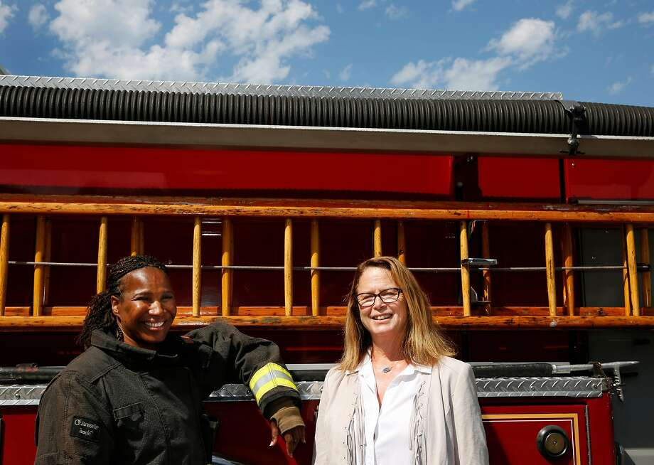 Shelia Hunter (left) and Frances Focha reminisce about their experiences of being among the city's first female fire fighters. Photo: Leah Millis, The Chronicle