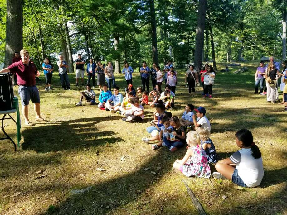 A member of the Audubon Society talks to Family First kids about birds at a barbecue on Sept. 17 in Bruce Park. Photo: Contributed