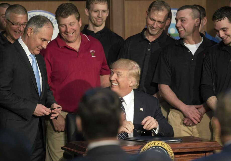President Donald Trump, flanked by coal miners, gives a pen to Scott Pruitt, administrator of the Environmental Protection Agency, as he signs an executive order directing the EPA to start the process of rewriting the Clean Power Plan. Call it the Trump-Pruitt Doctrine — ignoring the causes of climate change while doing nothing to halt it. Photo: STEPHEN CROWLEY /NYT / Stratford Booster Club