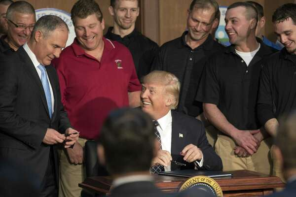 President Donald Trump, flanked by coal miners, gives a pen to Scott Pruitt, administrator of the Environmental Protection Agency, as he signs an executive order directing the EPA to start the process of rewriting the Clean Power Plan. Call it the Trump-Pruitt Doctrine — ignoring the causes of climate change while doing nothing to halt it.