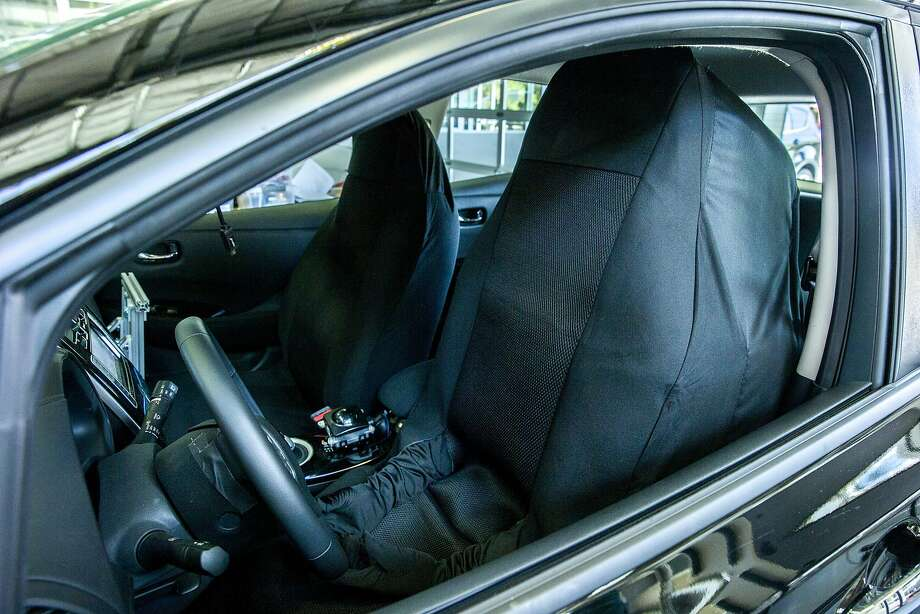 Graduate student Lawrence Domingo conceals himself as a car seat at Stanford University as part of a study to gauge the public's reaction to driverless vehicles. Photo: Santiago Mejia, The Chronicle