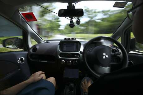FILE: - In this file photo from Wednesday, Aug. 24, 2016, a driver, right, gets his hands off of the steering wheel of an autonomous vehicle during its test drive in Singapore. Autonomous vehicle software startup nuTonomy has made rides on its self-driving taxis available to the general public in Singapore for free, expanding a first-in-the world run that was initially invitation-only. (AP Photo/Yong Teck Lim, File)