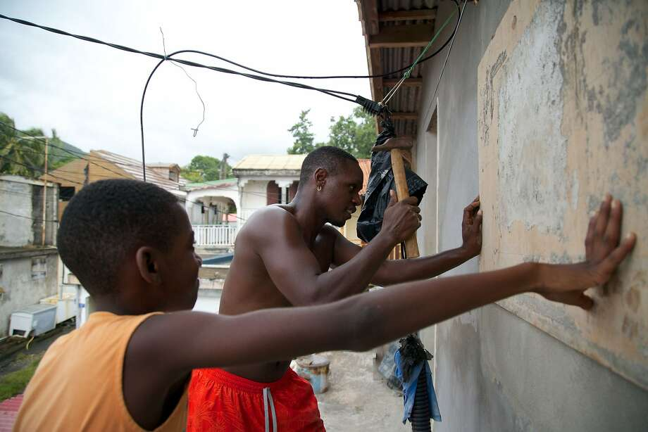"""A man and a boy nail a board over a window on September 18, 2017, in Basse-Terre, on the Fench Caribbean island of Guadeloupe, as Hurricane Maria approaches the Caribbean.  Hurricane Maria strengthened rapidly on September 18 as it blasted towards the eastern Caribbean, forcing exhausted islanders -- still recovering from megastorm Irma -- to brace for the worst again. The US National Hurricane Center (NHC) said the """"major hurricane"""" had intensified to Category 3 as it approached the French island of Guadeloupe, the base for relief operations for several islands devastated by Irma this month.   / AFP PHOTO / Cedrick Isham CALVADOSCEDRICK ISHAM CALVADOS/AFP/Getty Images Photo: CEDRICK ISHAM CALVADOS, AFP/Getty Images"""