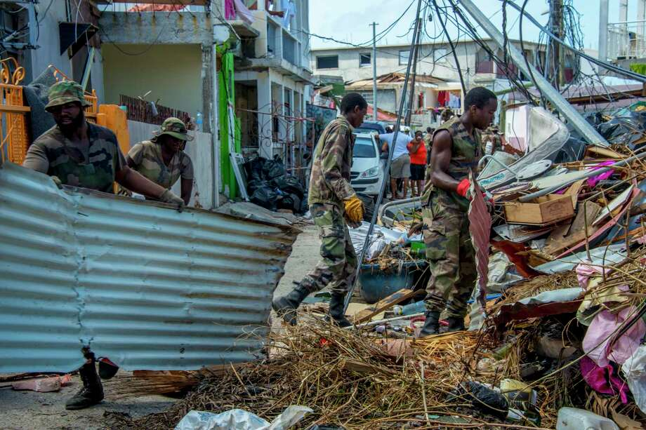 Members of the Guadeloupe Adapted Military Service Regiment clean up debris left by Hurricane Irma on the Caribbean island of St. Martin in advance of Hurricane Maria, which is on a path similar to Irma. Photo: HELENE VALENZUELA, Contributor / AFP or licensors