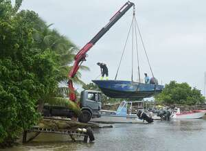 Men remove boats from the water ahead of Hurricane Maria in the Galbas area of Sainte-Anne on the French Caribbean island of Guadeloupe, early Monday, Sept. 18, 2017. Hurricane Maria grew into a Category 3 storm on Monday as it barreled toward a potentially devastating collision with islands in the eastern Caribbean. (AP Photo/Dominique Chomereau-Lamotte)