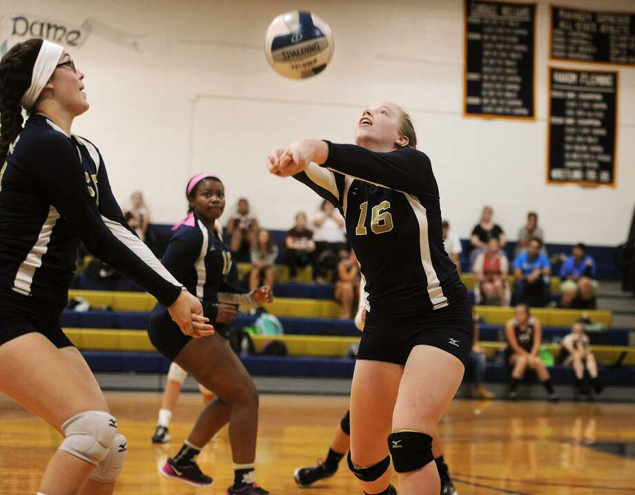 Notre Dame of Fairfield's Meghan Burke, right, sets the ball as teammate Olivia Ceballos, left, looks on during their victory over Bethel Monday in Fairfield. Photo: Brian A. Pounds / Hearst Connecticut Media / Connecticut Post