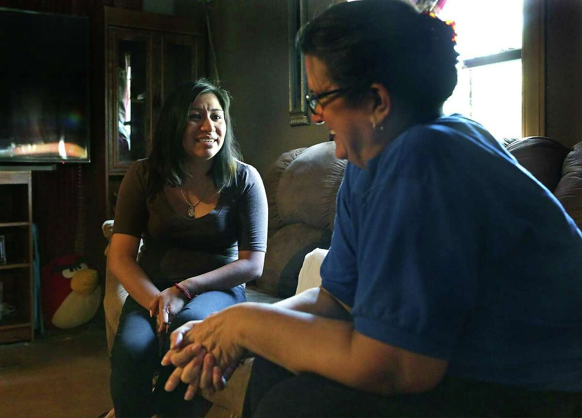 Yamilet Martinez (left) talks to Terry Escalante, a parent educator with House of Neighborly Service, about her children's health and education during an in-home visit.