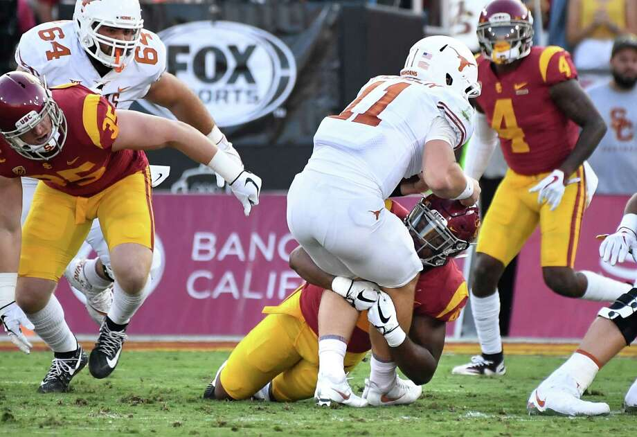 Southern Cal linebacker Uchenna Nwvosu stops Texas quarterback Sam Ehlinger on fourth down in the first quarter, part of a dismal rushing performance by the Longhorns on Saturday night. Photo: Wally Skalij, MBR / Los Angeles Times