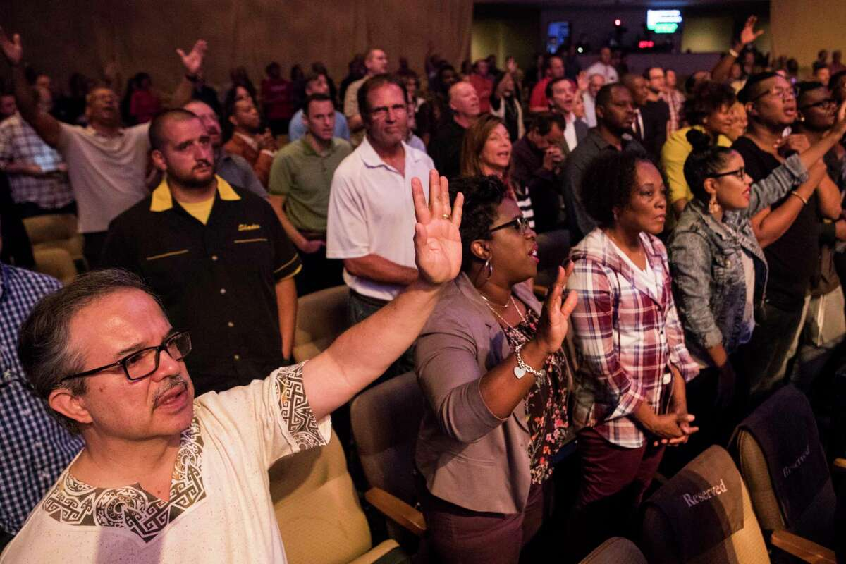 Congregants pray during a gathering of local pastors at First Baptist Church on Monday, encouraging them in long-term Hurricane Harvey recovery efforts.