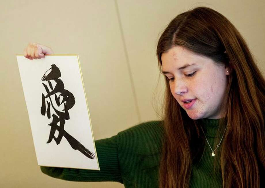 Sarah Brandstadt, 17, shows off a Japanese character during a recent presentation at the Midland Country Club by a group of Midland students about their trip to Midland's sister city of Handa, Japan. (Josie Norris/for the Daily News)