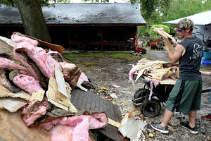 Ryan Long unloads debris while helping clean up his parents' house in Rose City on Monday.  Photo taken Monday 9/18/17 Ryan Pelham/The Enterprise