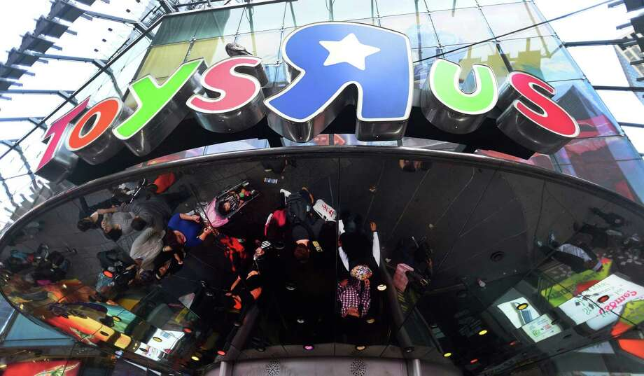 """Customers gather in front of the Toys """"R"""" Us Times Square flagship store in New York. Retailer Toys """"R"""" Us filed on Tuesday for Chapter 11 bankruptcy protection in a U.S. court, the company said, amid heavy debt and a tough environment for bricks and mortar stores. Photo: Don Emmert /AFP /Getty Images / AFP or licensors"""
